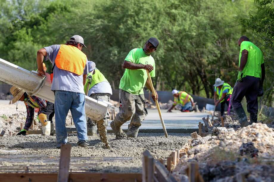 Construction workers with Clearfield Construction pour concrete for the City of Converse's new Greenway Trail in Converse City Park on July 17. Photo: Marvin Pfeiffer /Staff Photographer / **MANDATORY CREDIT FOR PHOTOG AND SAN ANTONIO EXPRESS-NEWS/NO SALES/MAGS OUT/TV