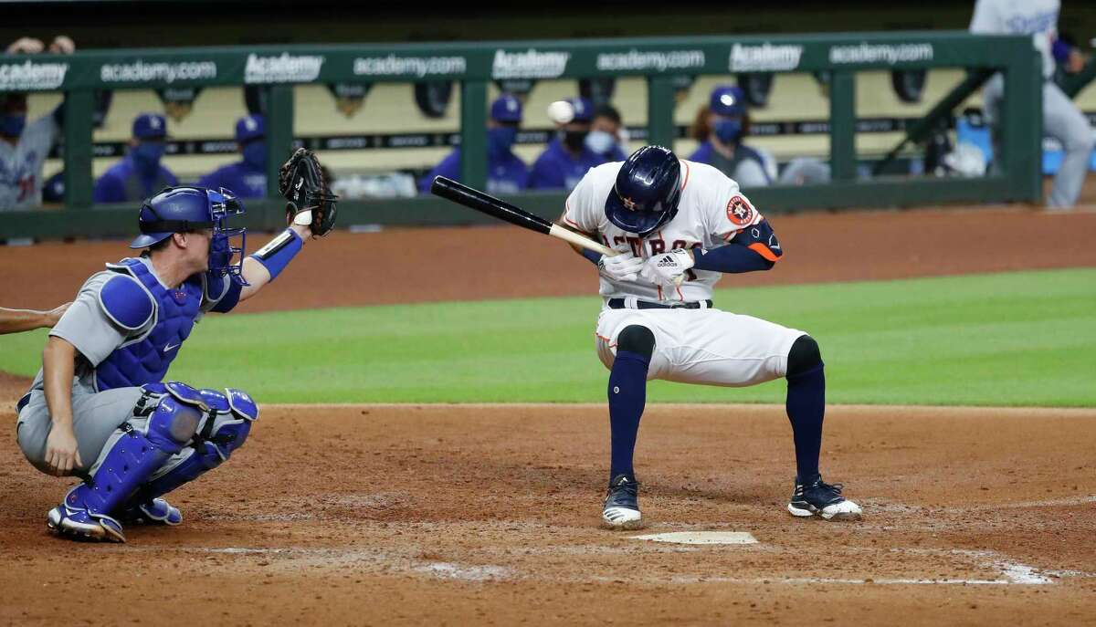 Houston Astros Carlos Correa dives down from a pitch from Los Angeles Dodgers relief pitcher Joe Kelly (17) during the sixth inning of an MLB baseball game at Minute Maid Park, Tuesday, July 28, 2020, in Houston.
