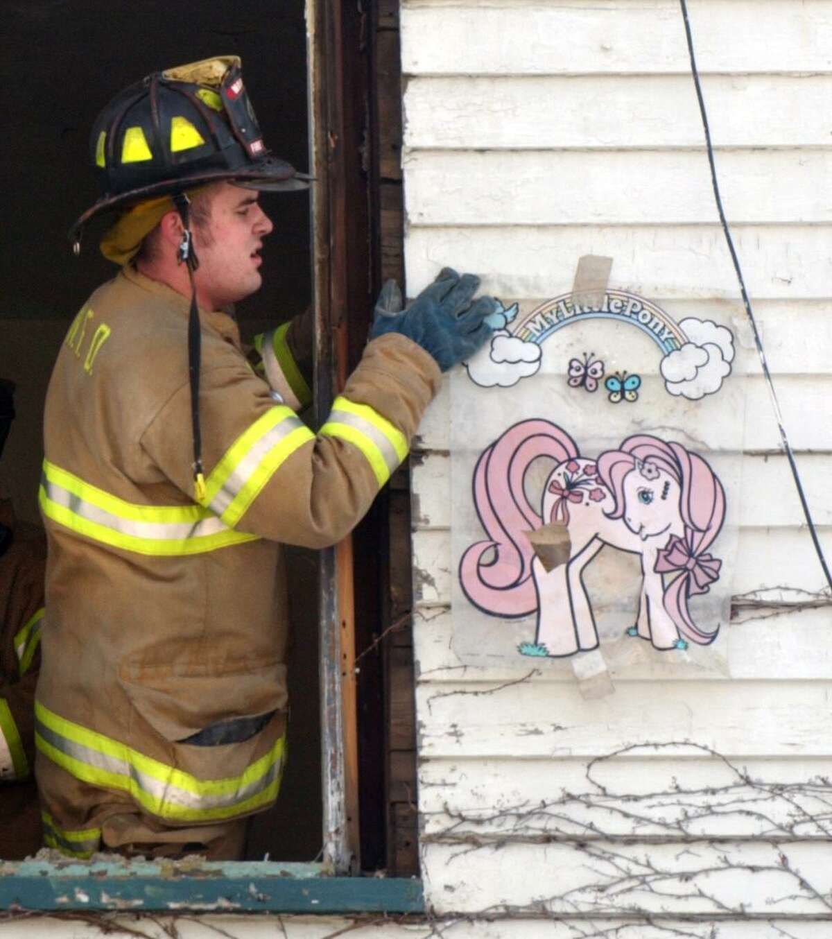 Norwalk firefighter Patrick St. Onge fixes a window decal on the outside of a Merwin Street home that was slated for demolition in 2014. St. Onge has been suspended for one week without pay after he was accused of making anti-Semitic comments in front of a Jewish member of the department.