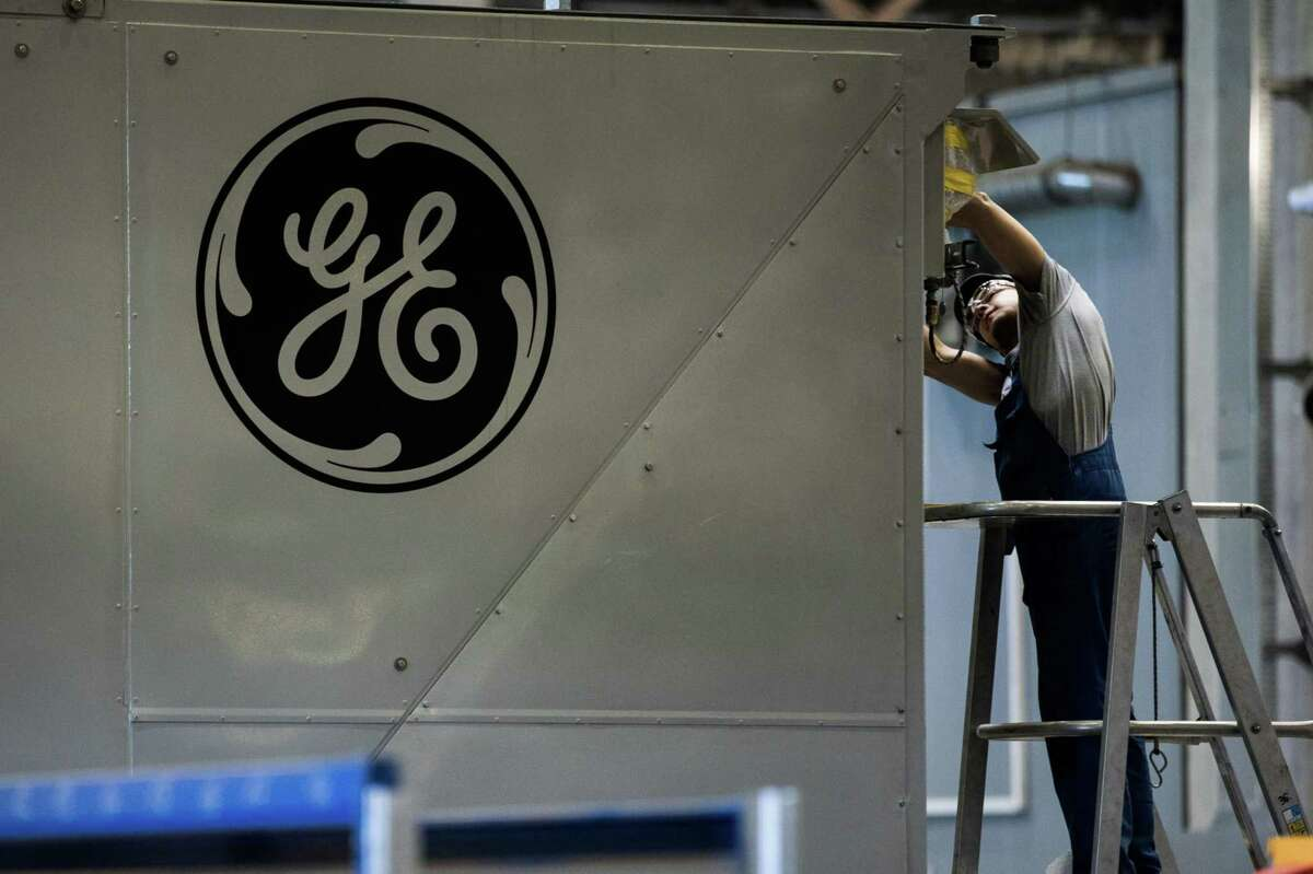 A GE logo sits on a panel as an employee works inside the General Electric Co. power plant in Veresegyhaz, Hungary, on June 13, 2017. MUST CREDIT: Bloomberg photo by Akos Stiller.