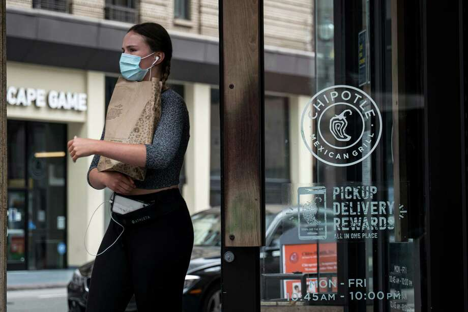 A customer wearing a protective mask exits a Chipotle Mexican Grill Inc. restaurant in San Francisco, California, U.S., on Monday, July 20, 2020. Digital pickup and delivery orders accounted for 61 percent of its sales in the most recent quarter. Photo: David Paul Morris / Bloomberg / © 2020 Bloomberg Finance LP