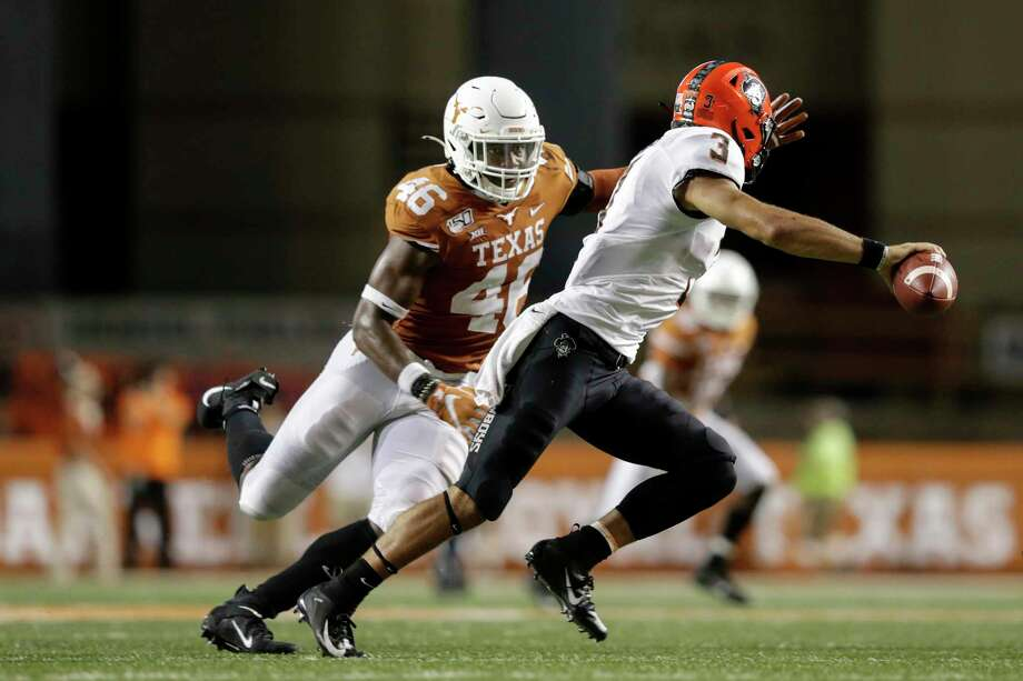 AUSTIN, TX - SEPTEMBER 21: Spencer Sanders #3 of the Oklahoma State Cowboys rolls out to pass under pressure by Joseph Ossai #46 of the Texas Longhorns in the fourth quarter at Darrell K Royal-Texas Memorial Stadium on September 21, 2019 in Austin, Texas. (Photo by Tim Warner/Getty Images) Photo: Tim Warner, Stringer / Getty Images / 2019 Getty Images