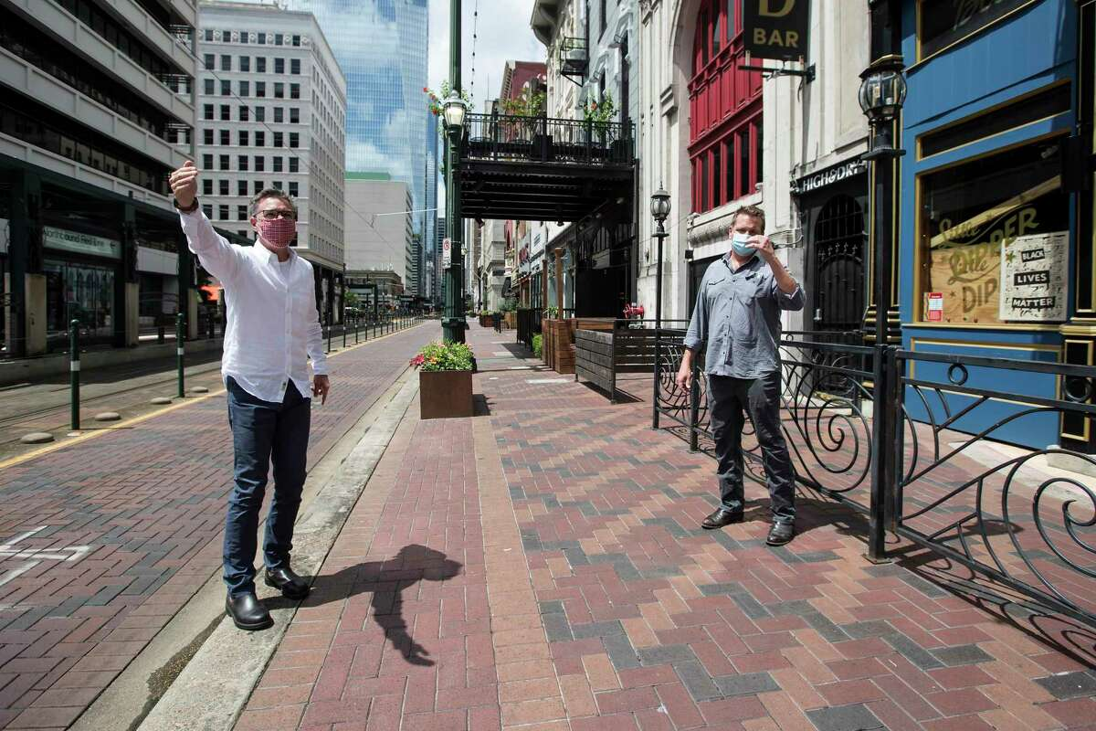Kinder Baumgardner, managing principal SWA, left, and Scott Repass, owner the Little Dipper, walk down Main Street as they talk about a proposal on July 27, 2020, to close the road to vehicular traffic in downtown Houston, so bars and restaurants can use the street to serve customers at a safe distance.