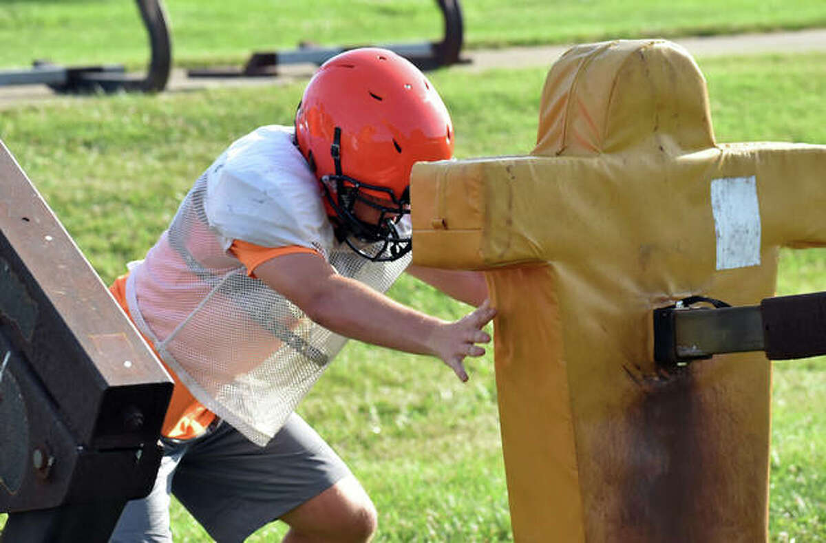 An Edwardsville High School football player runs through a drill during a summer practice inside the District 7 Sports Complex.