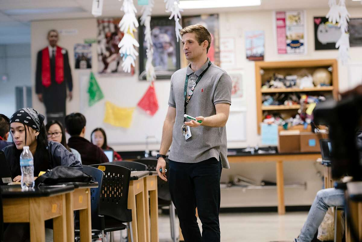 Teacher Evan Mundahl talks with students in his 11th grade Health Sciences class as they work on research about the Coronavirus, at the Phillip Burton Academic School in San Francisco, California, US, on Friday, March 13, 2020. The San Francisco Unified School District announced it would close schools for three weeks amid coronavirus concern starting on Monday, March 16th.