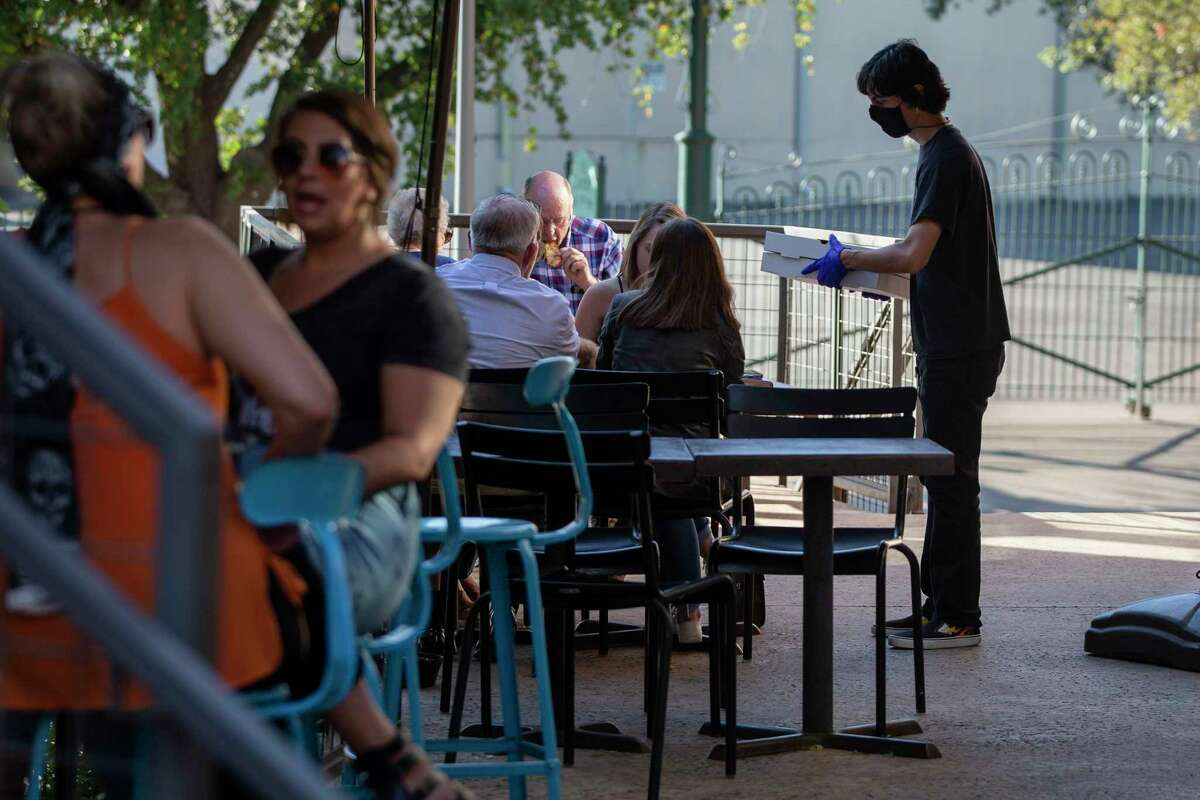 A server gives takeout boxes to people eating on the patio of Stella Public House at Blue Star Art Complex on June 12, 2020. San Antonio saw 47,000 more people return to work in June, sending the metro area unemployment rate down to 8.5 percent from 12.7 percent in May, the Bureau of Labor Statistics reported.