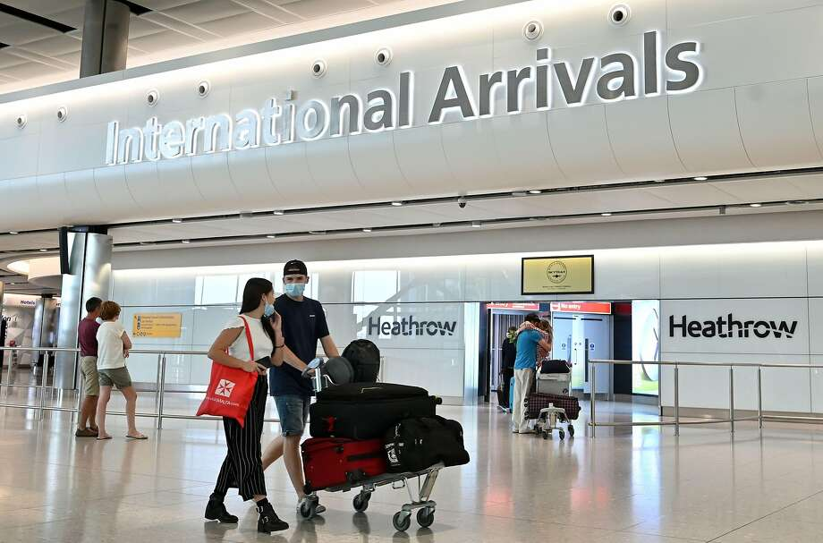 (FILES) In this file photo taken on May 09, 2020 Passengers wearing PPE (personal protective equipment), including a face mask as a precautionary measure against COVID-19, walk through the arrivals hall after landing at at Terminal Two of London Heathrow Airport in west London. - (Photo by JUSTIN TALLIS / AFP) (Photo by JUSTIN TALLIS/AFP via Getty Images) Photo: Justin Tallis, AFP Via Getty Images