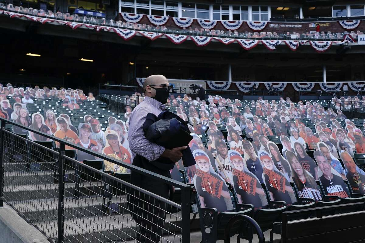San Francisco Giants president of baseball operations Farhan Zaidi stands in front of cardboard cutouts at Oracle Park before a baseball game between the Giants and the San Diego Padres in San Francisco, Tuesday, July 28, 2020.