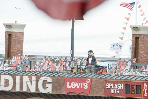 Giants mascot Lou Seal looks at the action with cardboard fan cutouts in the arcade seats of the stadium. Photo: Douglas Zimmerman/SFGATE / SFGATE