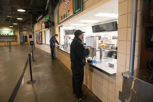 One food vendor was open, providing meals for the media and Giants staff working at the game. Sneeze guards were placed in-between the workers and customers. Photo: Douglas Zimmerman/SFGATE / SFGATE