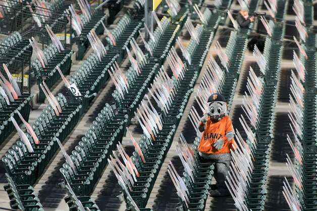 In the bottom of the sixth with the Giants rallying, mascot Lou the Seal attempts to lead cardboard cutouts in a  cheer. Photo: Douglas Zimmerman/SFGATE / SFGATE
