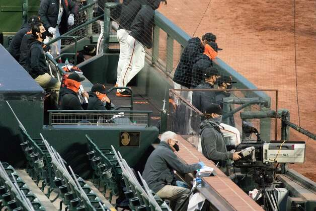 In the San Francisco Giants dugout, players and coaches wear face masks. A nearby television cameraman had a plastic sneeze guard placed between him and the dugout to protect against any possible infection of the coronavirus. Photo: Douglas Zimmerman/SFGATE / SFGATE
