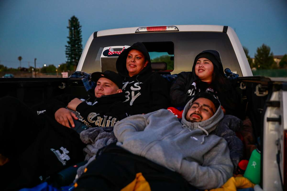 (L-r) Giovanni H. 16, Nancy S., Rene H. and Alejandra H., 24, watch The Shining from the back of their truck at the Drive In theater at the San Mateo County Event Center on Saturday, July 18, 2020 in San Mateo, California.