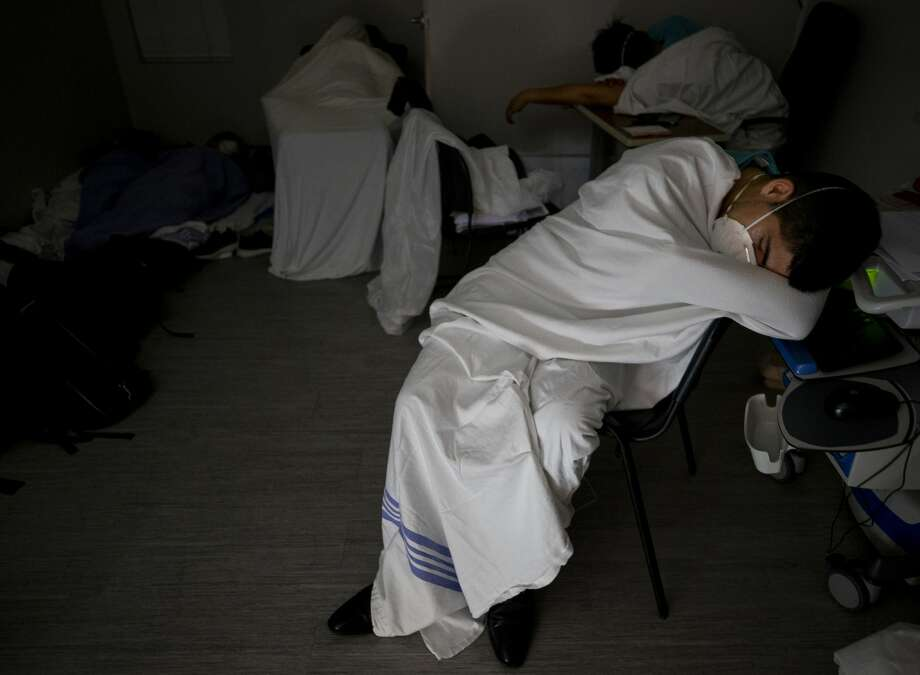 After working roughly 20 hours, medical interns sleep in the intern room inside the COVID-19 intensive care unit at UMMC on June 29, 2020. They slept intermittently for about three hours. Photo: Godofredo A. Vásquez/Staff Photographer / ? 2020 Houston Chronicle