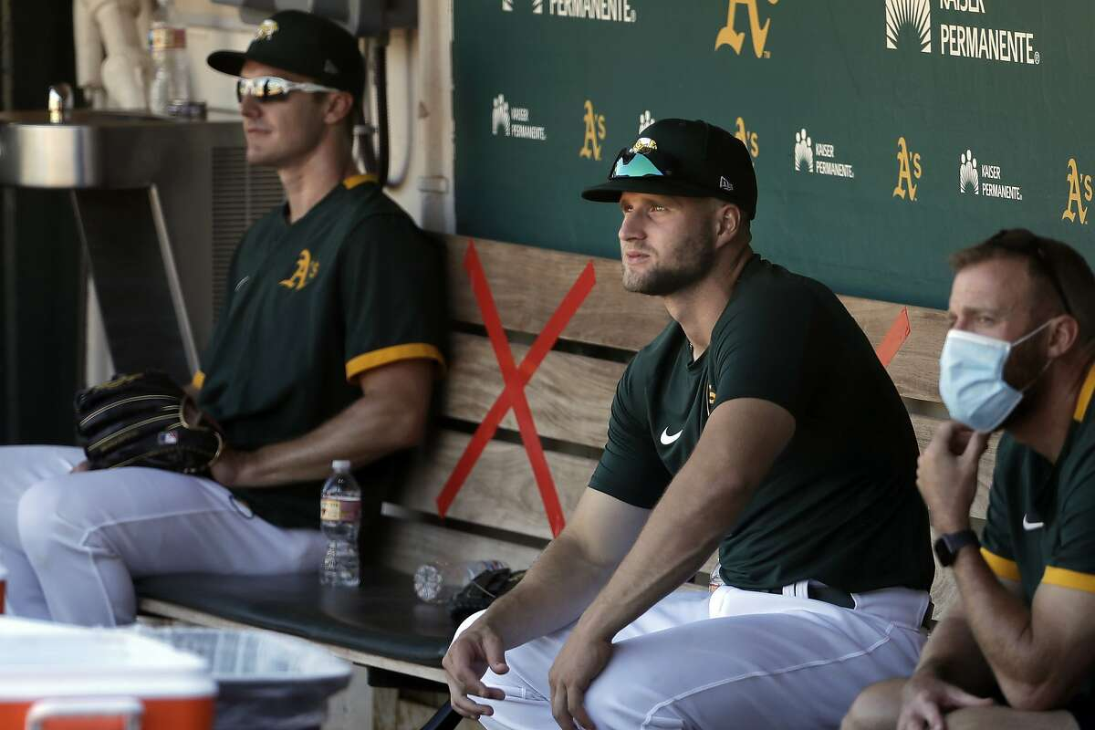 Tape marks places on the bench in the dugout between Oakland Athletics' Mark Canha, left, and Seth Brown during a baseball practice in Oakland, Calif., Saturday, July 11, 2020. (AP Photo/Jeff Chiu)