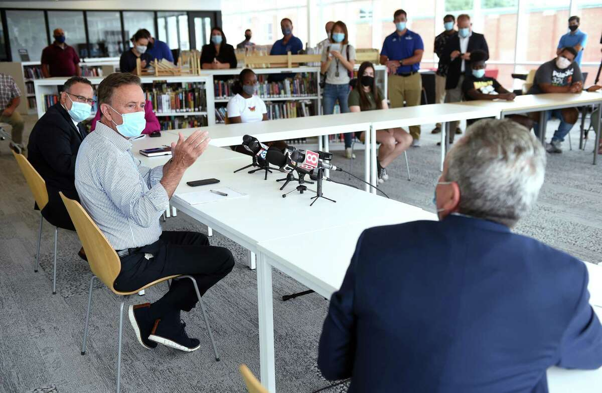Seated from left, Connecticut Education Commissioner Miguel Cardona, Governor Ned Lamont and West Haven Superintendent of Schools Neil Cavallaro meet with students at West Haven High School on July 24, 2020.