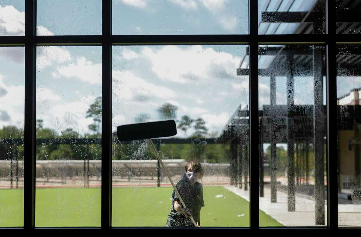 A woman washes windows during a tour of the new Donald J. Stockton Junior High School, Wednesday, July 29, 2020, in Conroe.