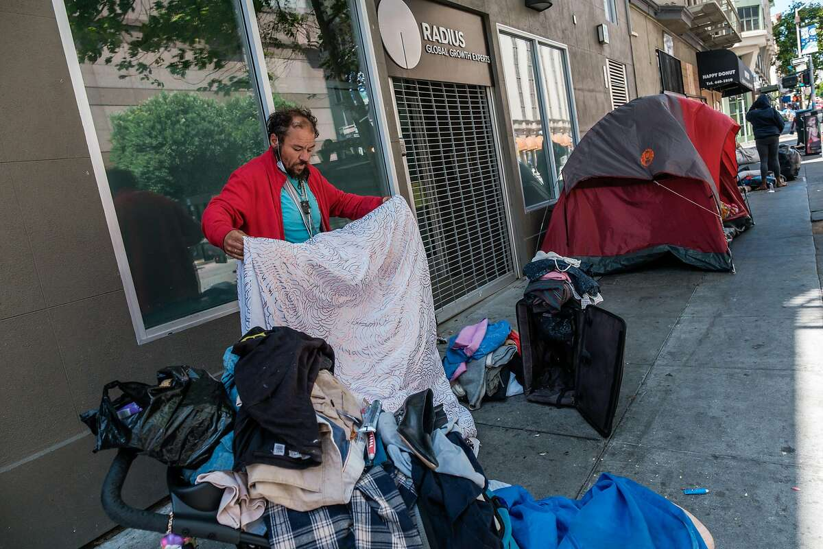 Eric Delahonssaye organizes his belongs near a small tent encampment on the corner of Taylor and Ellis in San Francisco on Tuesday, July 2, 2020. Mr. Delahonssaye is waiting to be moved into a hotel being made available to homeless.