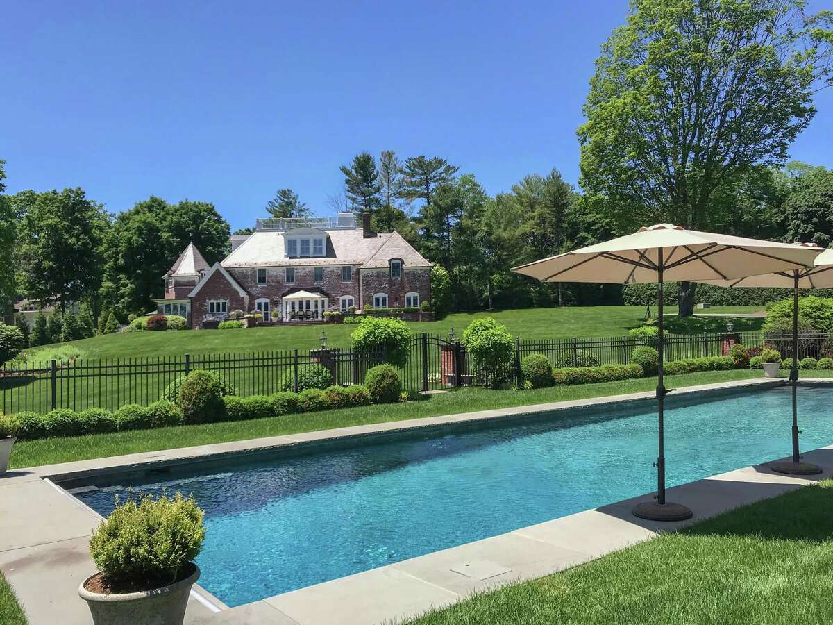The white-washed red brick French Normandy Chateau-style house at 1135 Mine Hill Road is like something out of the French countryside and the pages of a fairytale. The 4.32-acre level and gently sloping property features a heated Gunite in-ground swimming pool and attractive landscaping.