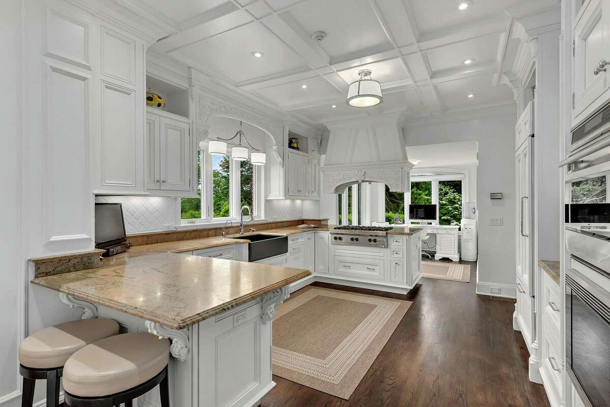 The new gourmet kitchen features a large center island/breakfast bar, ogee-edged granite counters, farm sink, coffered ceiling, decorative moldings, and high-end appliances.