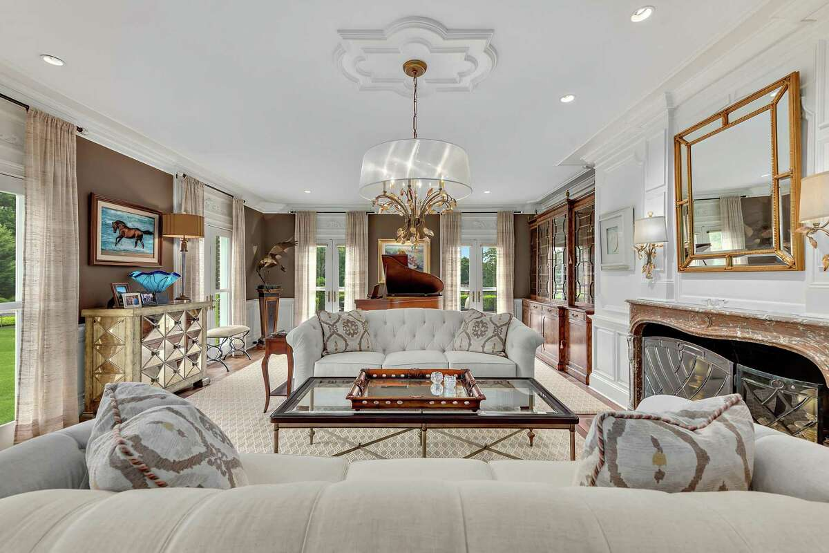 In the spacious formal living room features include a marble fireplace, sophisticated millwork and molding, and several sets of French doors to the beautiful grounds. Red brick pillars stand at the entrance to this gated property. Its long paved driveway is lined with a double border of Belgium block and leads to the detached four-car garage and then to the main house and the carriage house, which includes five more vehicle bays; perfect for a vintage car collector. If not cars, this space could be converted into a private office, art or recording studio, or a guest cottage, in-law or au pair suite. One of the three-story turrets could also serve any of these purposes as well.