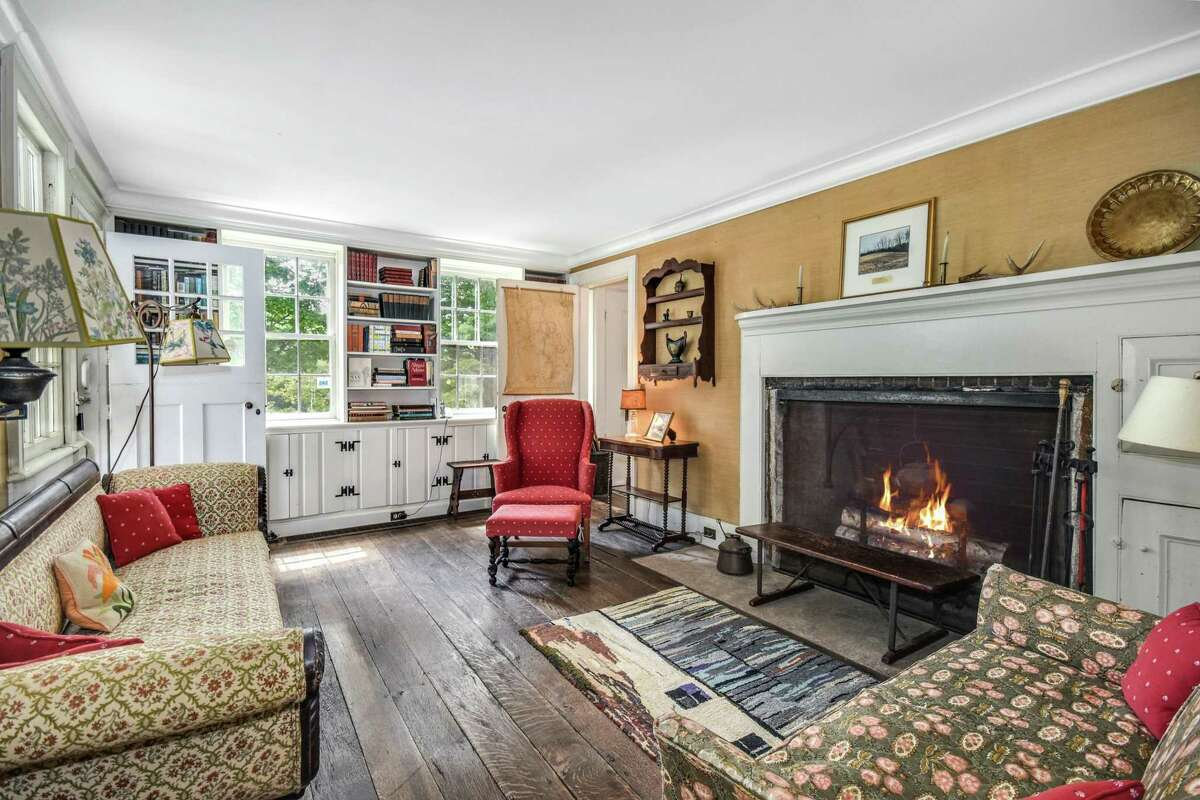 The den features a fireplace, cabinetry, bookshelves, and original wide-planked hardwood flooring.
