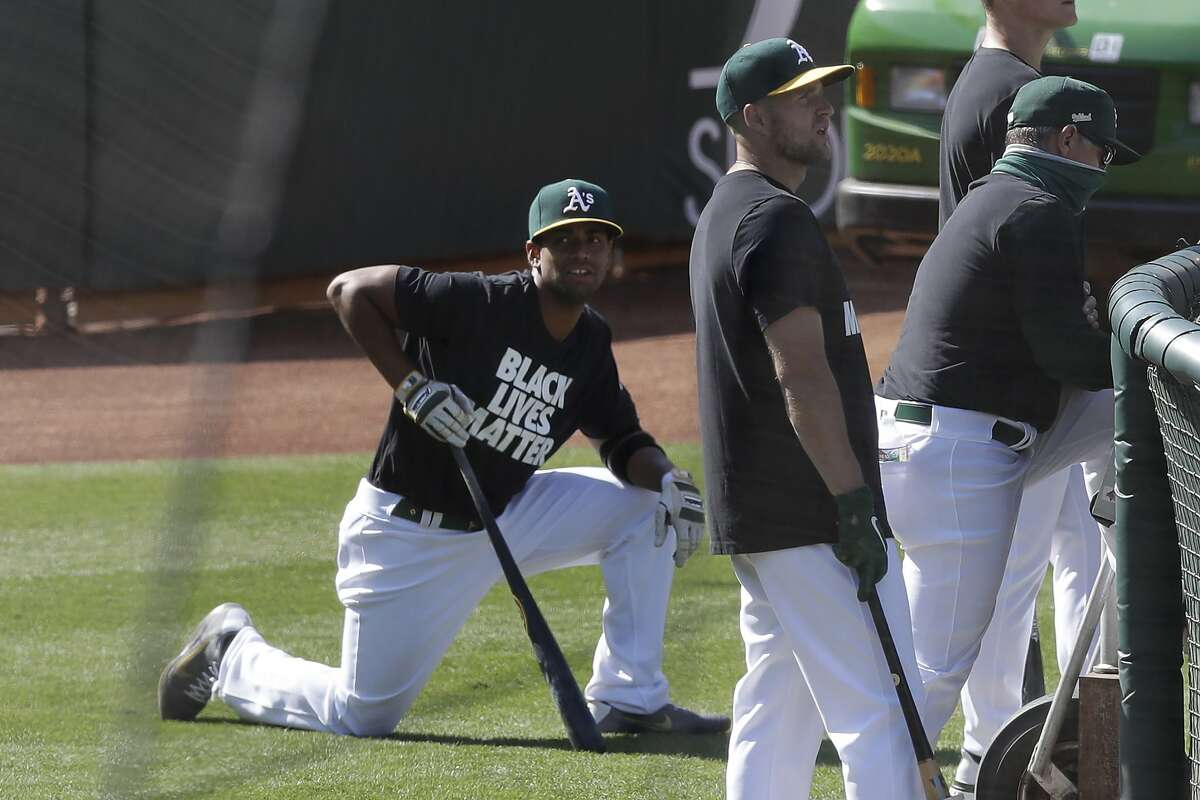 """Oakland Athletics' Khris Davis, left, and teammates wear shirts that read """"Black Lives Matter"""" before a baseball game against the Los Angeles Angels in Oakland, Calif., Friday, July 24, 2020. (AP Photo/Jeff Chiu)"""