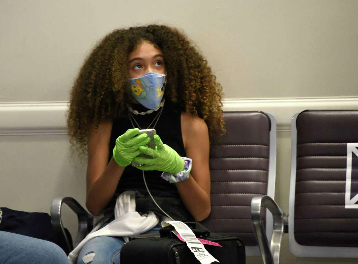 A woman is seen wearing a face mask and gloves at a gate at Albany International Airport on Wednesday, July 29, 2020 in Colonie, N.Y. (Lori Van Buren/Times Union)