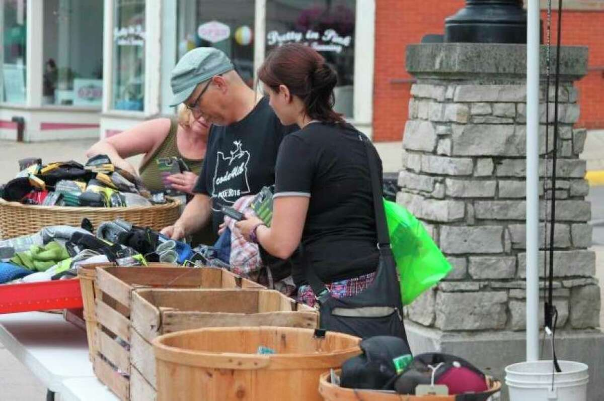 Shoppers crowd around items that The Outpost had out for the annual Manistee Sidewalk Sale in 2016. The event drew large crowds to River Street throughout the day. (File photo)