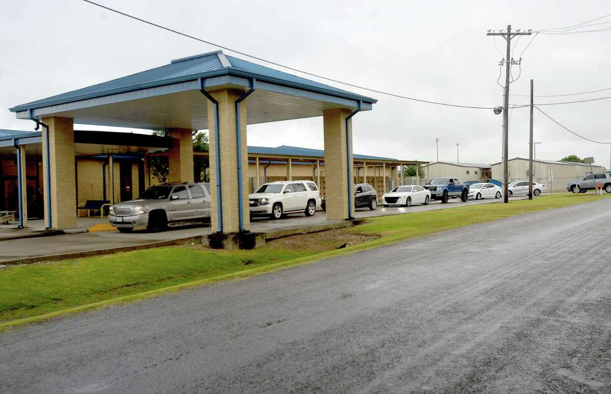 Cars line up to get tested for COVID-19 at Hamshire - Fannett High School Friday. The district is offering free tests for all students and requiring them for athletes who will participate in summer workouts. Photo taken Friday, July 17, 2020 Kim Brent/The Enterprise