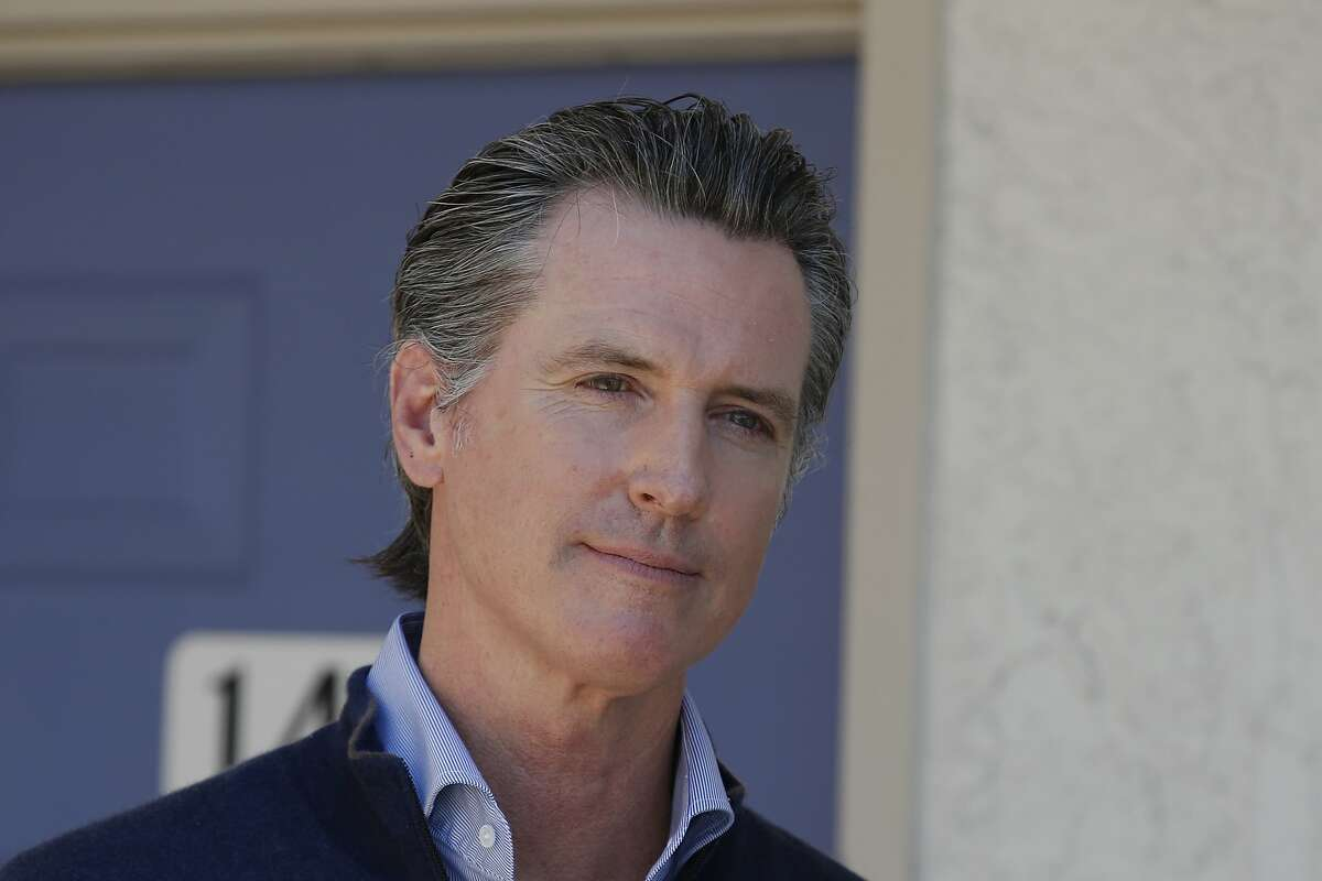 """FILE - In this June 30, 2020 file photo Gov. Gavin Newsom listens to a reporters question during a news conference in Pittsburg, Calif. California will raise its minimum wage to $14 an hour next year for workers at larger companies, hitting businesses with higher costs even at a time when many are struggling amid the coronavirus pandemic. """"Not allowing this increase to go forward will only make life harder for those Californians who have already borne a disproportionate share of the economic hardship caused by this pandemic,"""" Newsom said. (AP Photo/Rich Pedroncelli, Pool,File)"""