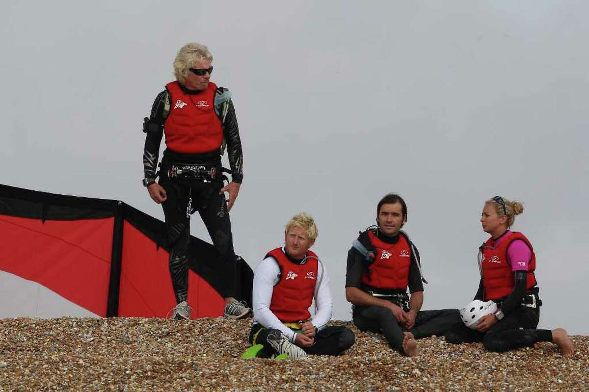 DUNGENESS, UNITED KINGDOM - AUGUST 25: Richard Branson (L) stands on the beach after failing in his attempt to Kite Surf across the English Channel on August 25, 2010 in Dungeness, England. Due to weather conditions, Mr Branson had to call off the attempt, which was to celebrate his 60th birthday, and have him become the oldest person to Kite-surf across the English Channel. (Photo by Dan Kitwood/Getty Images) *** Local Caption *** Richard Branson