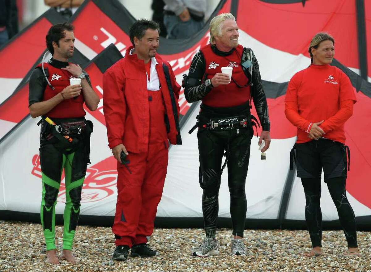 DUNGENESS, UNITED KINGDOM - AUGUST 25: Richard Branson (2nd-R) stands on the beach after failing in his attempt to Kite Surf across the English Channel on August 25, 2010 in Dungeness, England. Due to weather conditions, Mr Branson had to call off the attempt, which was to celebrate his 60th birthday, and have him become the oldest person to Kite-surf across the English Channel. (Photo by Dan Kitwood/Getty Images) *** Local Caption *** Richard Branson