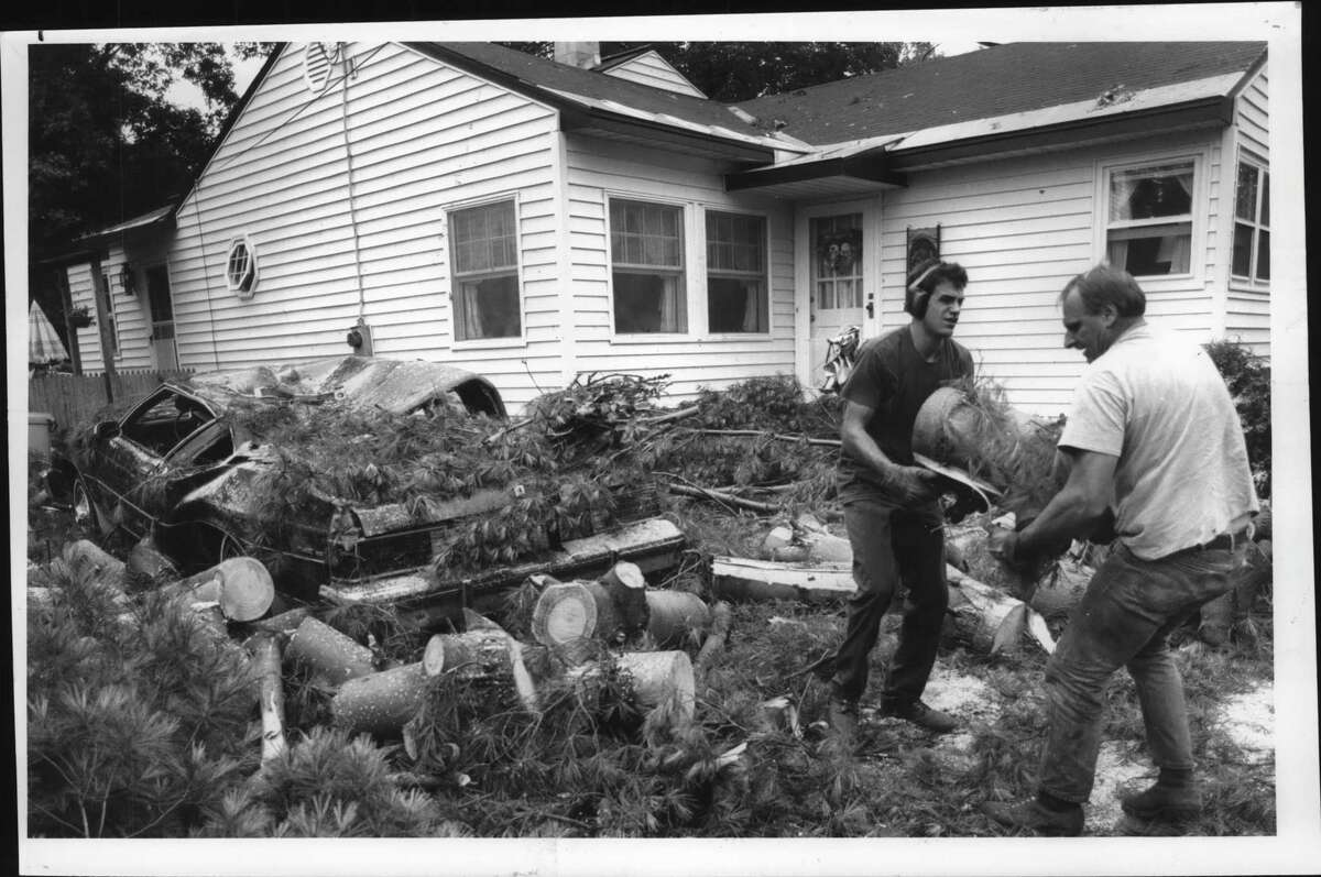 Tree service workers remove a tree from the crushed 1983 Buick owned by a Cosby Street, Colonie resident after the it was blown over during a storm on July 30, 1992. (Paul Kniskern/Times Union Archive)