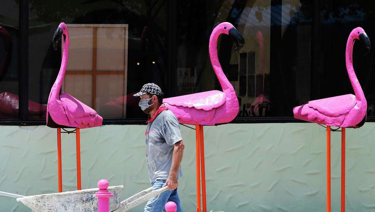 Hector Valdez dons a mask as he works on a construction site at Deco Pizzeria where he passes by a trio of flamingo statues on Wednesday, July 28, 2020.