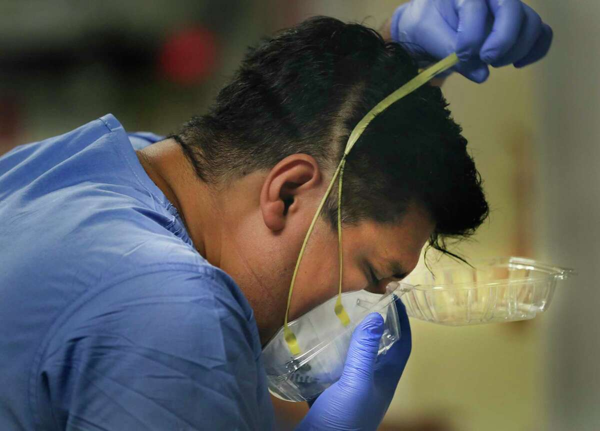 """Nurse Julio Gaona removes his N95 mask, putting it into a """"to-go-box"""" to keep from contaminating surfaces at Methodist Hospital. San Antonio has had a massive influx of coronavirus patients into its hospitals, on Thursday, June, 25, 2020."""