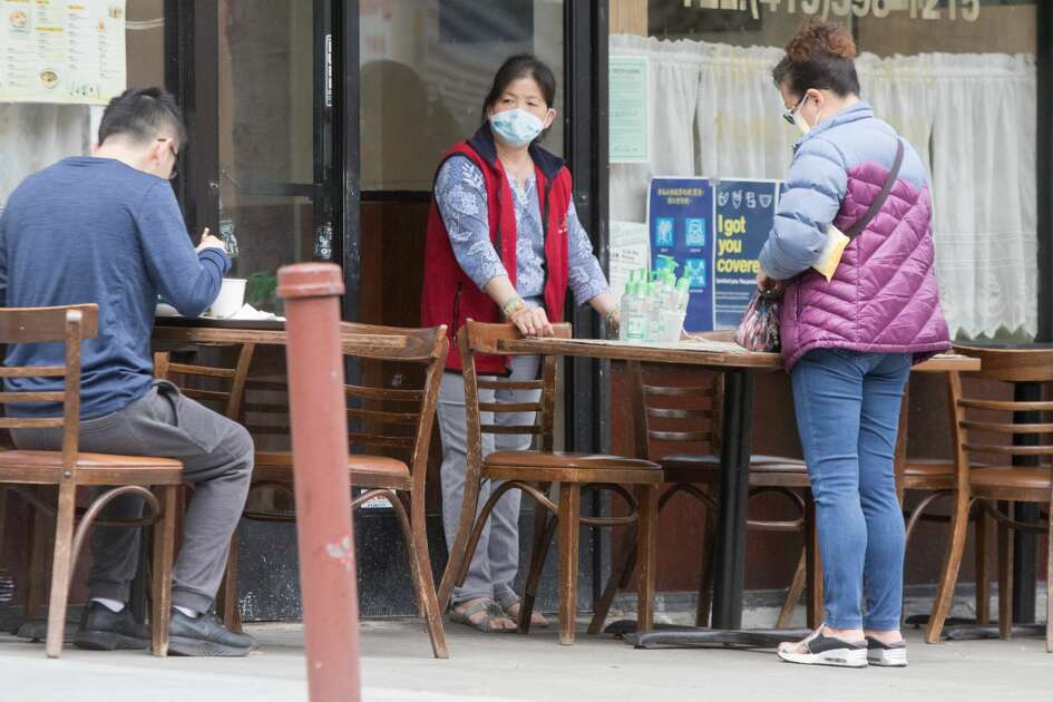 A shop owner delivers a to-go order to a customer. Pedestrians Most people wear masks protect themselves from the COVID-19 coronavirus in San Francisco?•s Chinatown neighborhood in San Francisco, Calif. on July 28, 2020.