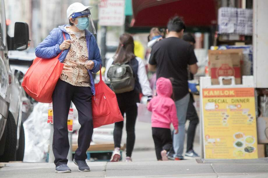 A shopper wears a mask and shield while shopping. Pedestrians wear masks to protect themselves from the COVID-19 coronavirus in San FranciscoÕs Chinatown neighborhood in San Francisco, Calif. on July 28, 2020. Photo: Douglas Zimmerman/SFGATE / SFGATE