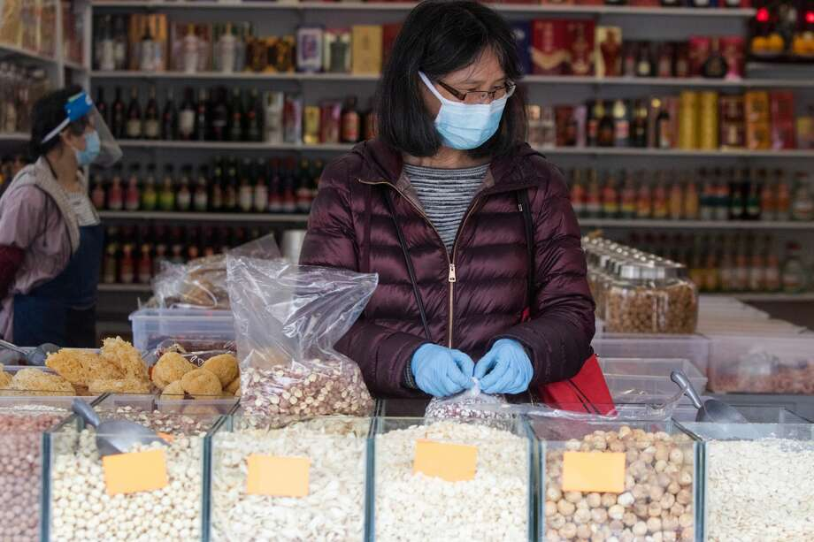 A woman selects nuts to buy at a store on Stockton Street. Shoppers wear masks to protect themselves from the COVID-19 coronavirus in San FranciscoÕs Chinatown neighborhood in San Francisco, Calif. on July 28, 2020. Photo: Douglas Zimmerman/SFGATE / SFGATE