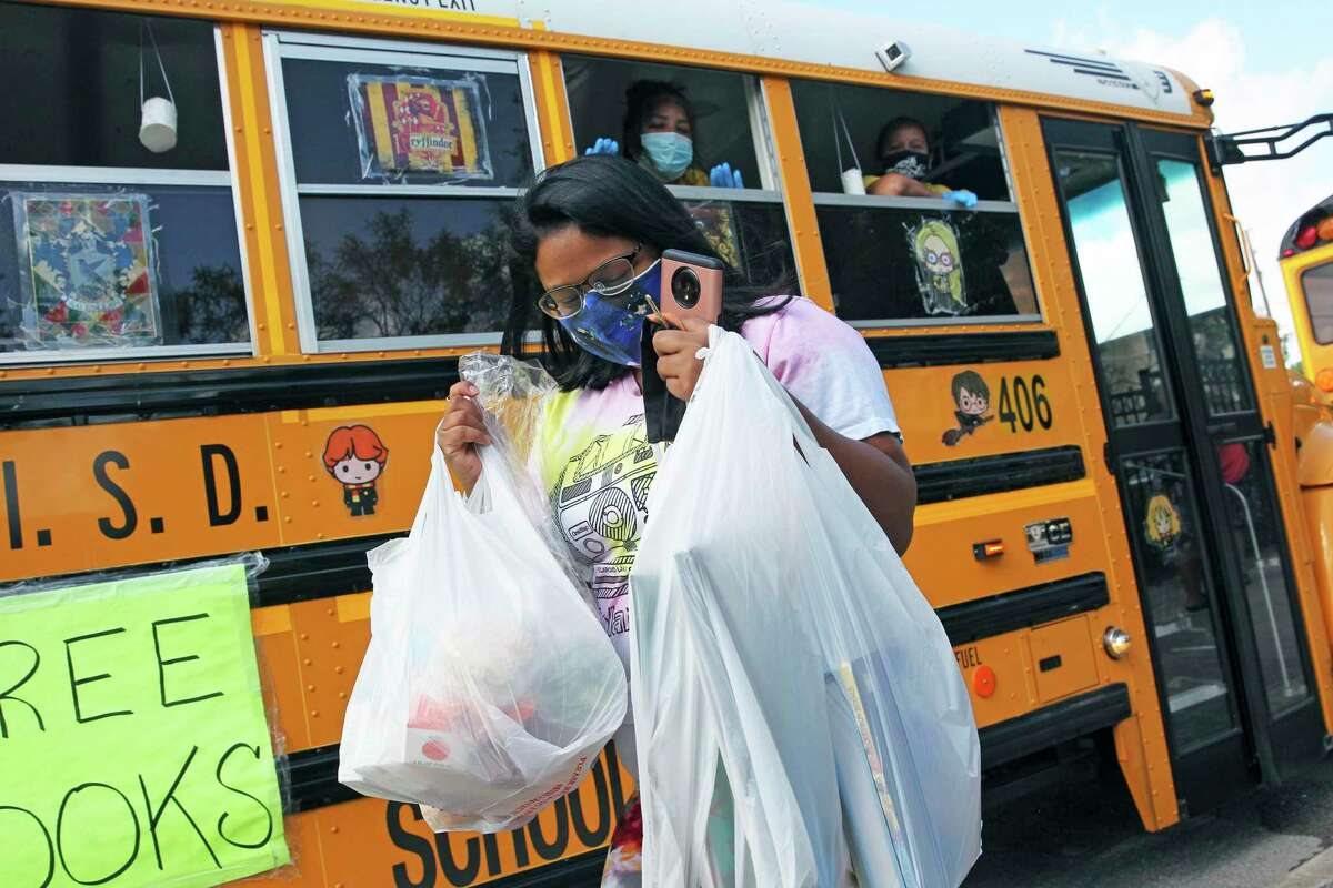 Victoria Ornelas hauls away lunch and some books as the SAISD Foundation gives away books from a school bus parked at the Rosemont Apartments on Rigsby to local residents on July 28, 2020. Workers in the bus are Lorraine Martinez and Oralia Santos.