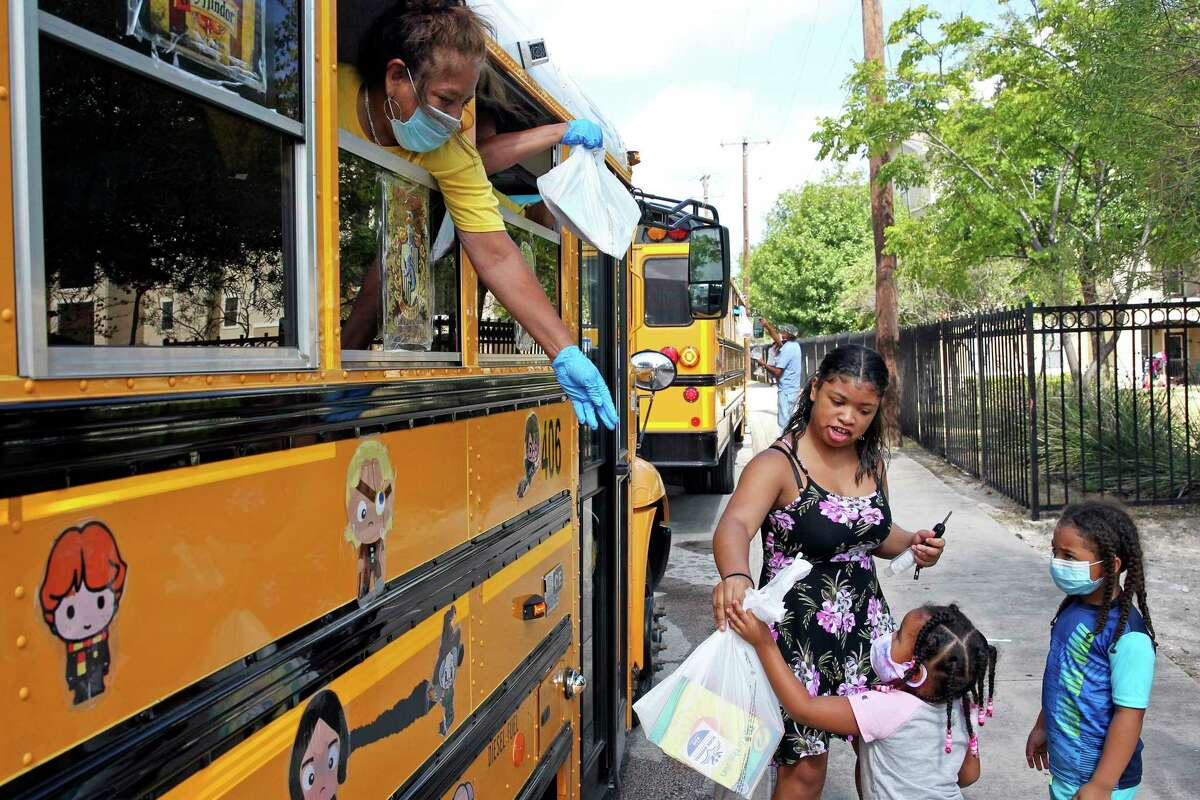 Oralia Santos hands out bags of reading material as the SAISD Foundation gives away books from a school bus parked at the Rosemont Apartments on Rigsby to local residents on July 28, 2020.
