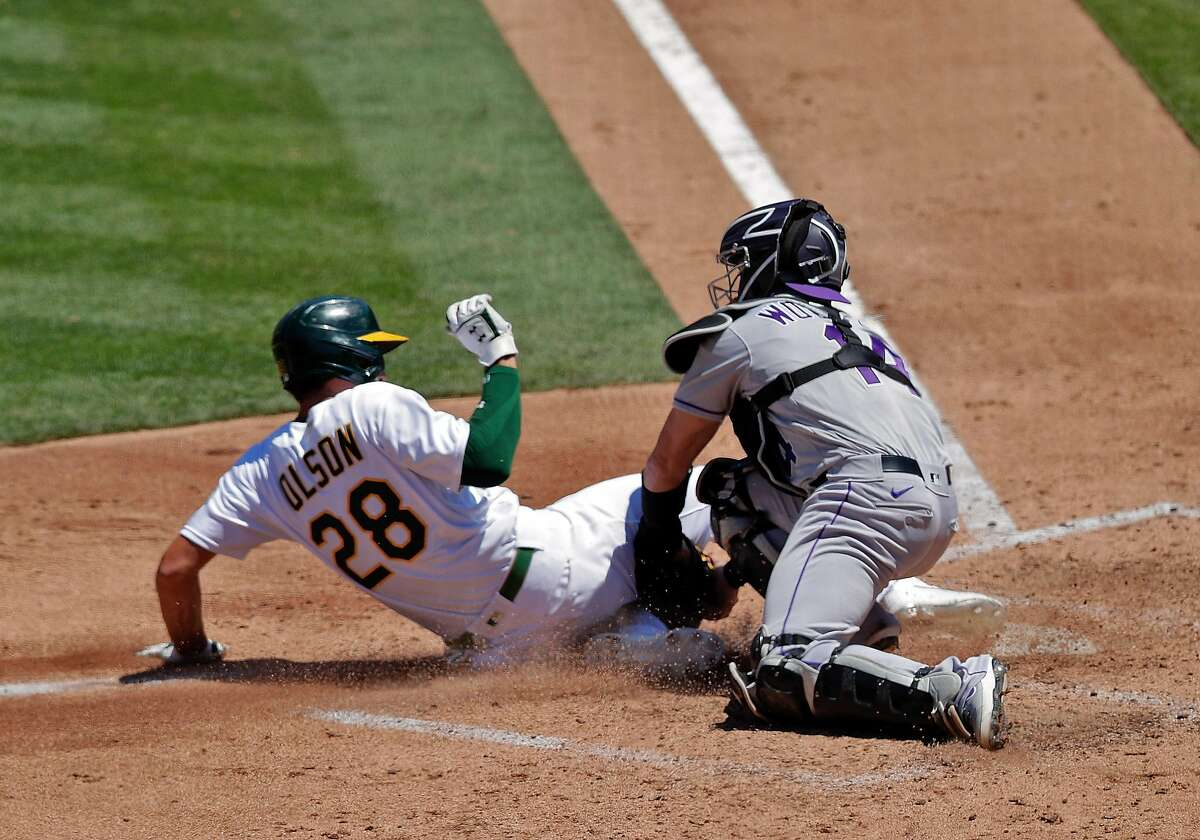 Matt Olson (28) out at the plate on a fielder's choice on a ball hit by Stephen Piscotty (25) in the fourth inning as the Oakland Athletics played the Colorado Rockies at the Coliseum in Oakland, Calif., on Wednesday, July 29, 2020.