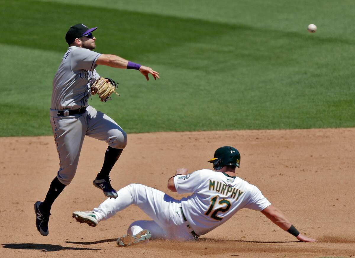 Garrett Hampson (1) throws over Sean Murphy (12) on a double play attempt in the fifth inning as the Oakland Athletics played the Colorado Rockies at the Coliseum in Oakland, Calif., on Wednesday, July 29, 2020.