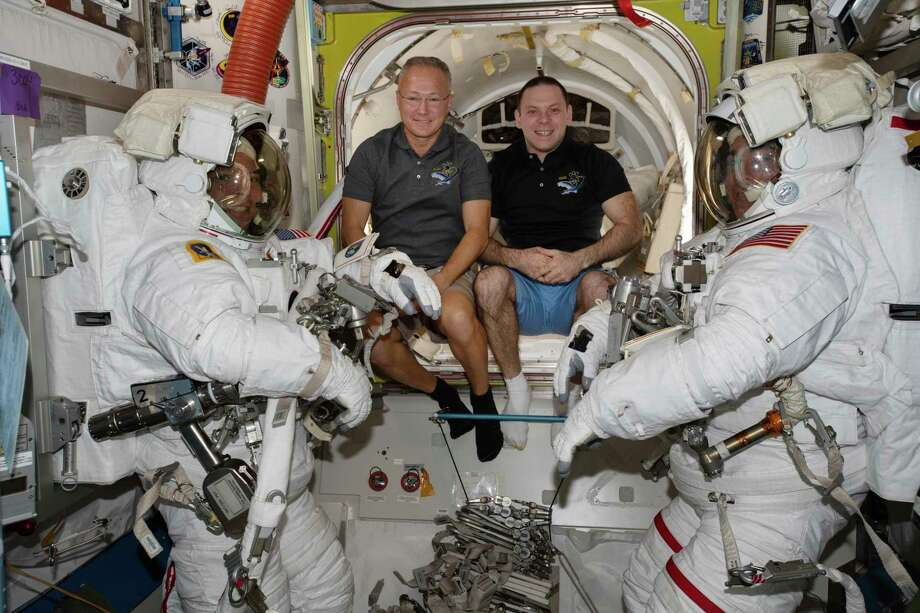 In this June 26, 2020 photo made available by NASA, spacewalkers Bob Behnken, foreground left, and Chris Cassidy, foreground right, are suited up with assistance from Expedition 63 Flight Engineers Doug Hurley, center left, and Ivan Vagner in the International Space Station. Photo: Associated Press / NASA
