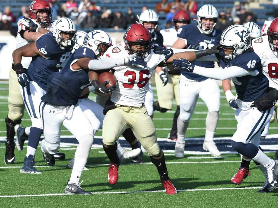 Harvard's Devin Darrington runs against Yale during the first half during a game in New Haven in November. Photo: Arnold Gold / Hearst Connecticut Media / New Haven Register