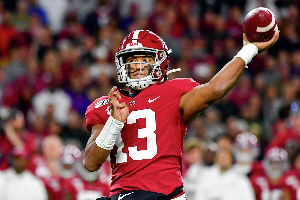 FILE - In this Nov. 9, 2019, file photo, Alabama quarterback Tua Tagovailoa throws during an NCAA football game in Tuscaloosa, Ala. The rookie quarterback has reported to Miami Dolphins training camp and will practice without restrictions as he comes back from a knee injury and begins to compete to overtake veteran Ryan Fitzpatrick for the starting job. (AP Photo/Vasha Hunt, File)