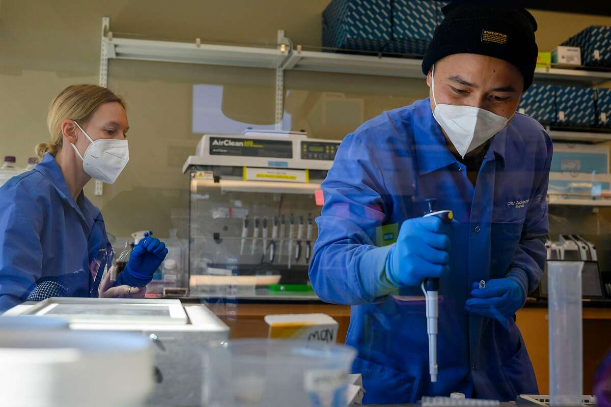 Scientist Ashley Byrne looks on as Research Associate Michael Borja runs an experiment on the RNA of a sample inside a lab at the Chan Zuckerberg Biohub on Wednesday, July 29, 2020 in San Francisco, Calif. Biohub, the medical research lab funded by Facebook CEO Mark Zuckerberg?•s philanthropic organization Chan Zuckerberg Initiative, is announcing that it will offer free genome sequencing for lab samples that have tested positive for the coronavirus, from all counties in California. According to Biohub, it?•s one of the largest statewide efforts to do genome sequencing for COVID-19.