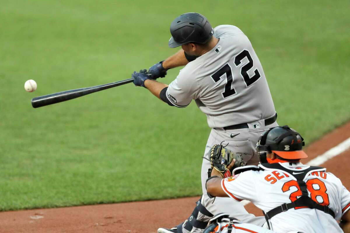 New York Yankees' Mike Ford (72) hits a sacrifice fly ball that allowed teammate Aaron Judge to score from third base on a pitch from Baltimore Orioles starting pitcher Asher Wojciechowski during the first inning of a baseball game, Wednesday, July 29, 2020, in Baltimore. (AP Photo/Julio Cortez)