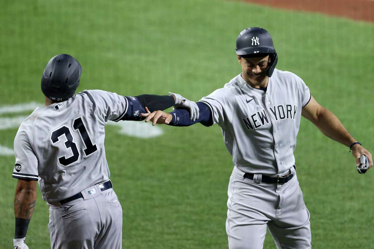 BALTIMORE, MARYLAND - JULY 29: Aaron Hicks #31 of the New York Yankees celebrates with Giancarlo Stanton #27 after hitting a two RBI home run against the Baltimore Orioles in the third inning at Oriole Park at Camden Yards on July 29, 2020 in Baltimore, Maryland. (Photo by Rob Carr/Getty Images)
