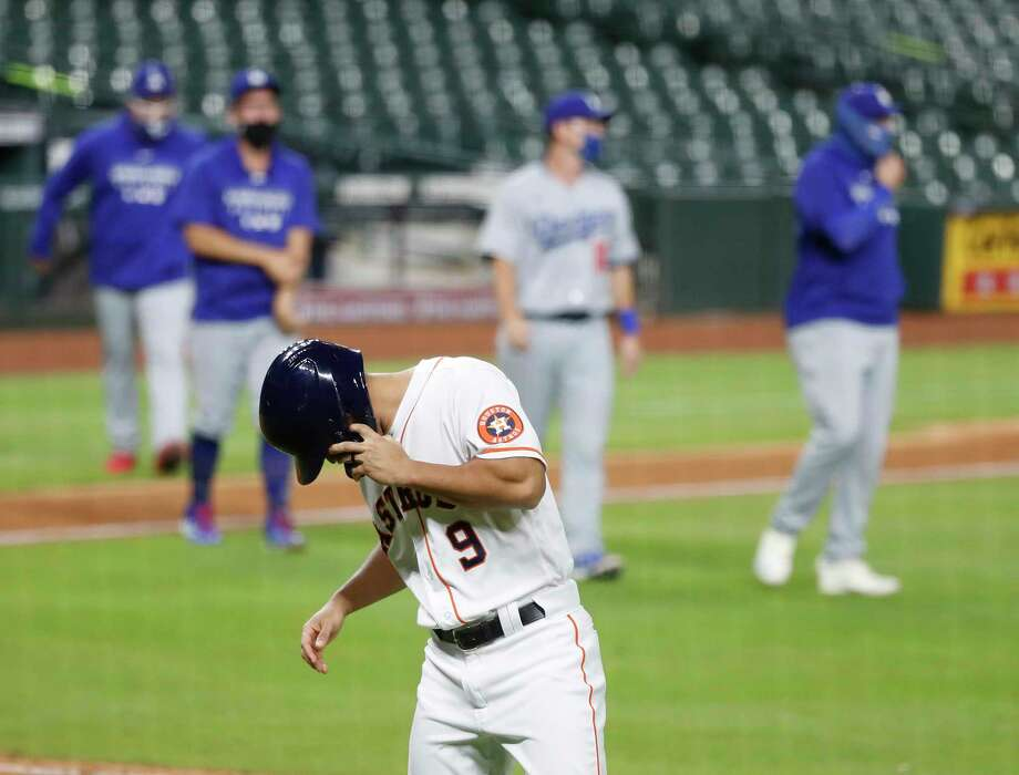 Houston Astros infielder Jack Mayfield walks back to the dugout as the Los Angeles Dodgers celebrate after the they beat the Astros 4-2 in the thirteenth inning of an MLB baseball game at Minute Maid Park, Wednesday, July 29, 2020, in Houston. Photo: Karen Warren, Staff Photographer / © 2020 Houston Chronicle